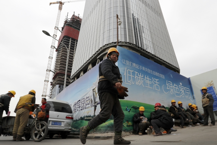 In this Dec. 13, 2016 photo, workers buy their lunch outside a construction site at the Central Business District in Beijing. China's economic growth accelerated slightly in the final quarter of 2016 but its full-year performance still was the weakest in nearly three decades. The government reported Friday, Jan. 20, 2017 the world's second-largest economy expanded by 6.8 percent in the fourth quarter over a year earlier, up from the previous quarter's 6.7 percent. Full-year growth was 6.7 percent, down from 2015's 6.9 percent and the weakest since 1990. (AP Photo/Andy Wong)