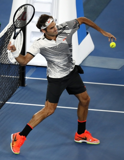 Switzerland's Roger Federer hits the ball into the stands as he celebrates his victory over Japan's Kei Nishikori at the Australian Open tennis championships in Melbourne, Australia, Sunday, Jan. 22, 2017. (AP Photo/Kin Cheung)