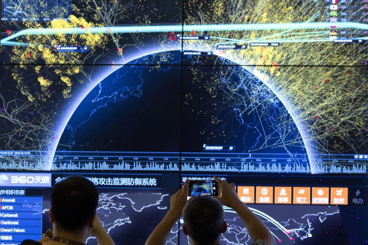 In this Aug. 16, 2016 photo, an attendee takes a photo of a visualization of global internet attacks during the 4th China Internet Security Conference (ISC) in Beijing. A Chinese technology regulator has announced Sunday, Jan. 23, 2017, a year-long campaign to root out services that allow people in the country to circumvent the government's Internet censorship. (AP Photo/Ng Han Guan)