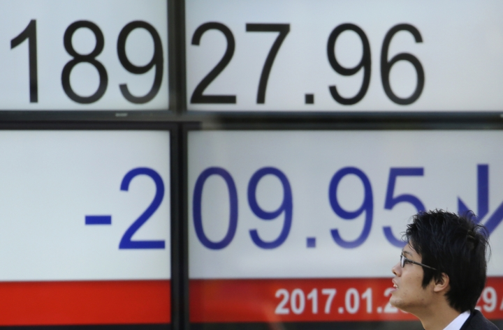 "A man looks at an electronic stock board of a securities firm in Tokyo, Monday, Jan. 23, 2017. Japanese stocks tumbled Monday after Donald Trump took office as U.S. president and promised ""American first"" policies, prompting concern about possible protectionism. (AP Photo/Koji Sasahara)"