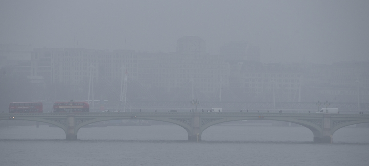 Two London transport buses make their way over Westminster Bridge on a foggy day in London, Monday, Jan. 23, 2017. Freezing fog covered the capital on Monday as cold weather conditions continued. (AP Photo/Alastair Grant)