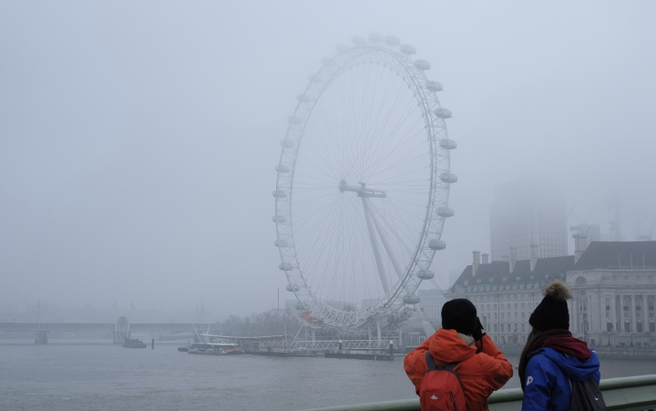 The London Eye ferris wheel is photographed by tourists who stand on Westminster Bridge on a foggy day in London, Monday, Jan. 23, 2017. Freezing fog covered the capital on Monday as cold weather conditions continued. (AP Photo/Alastair Grant)