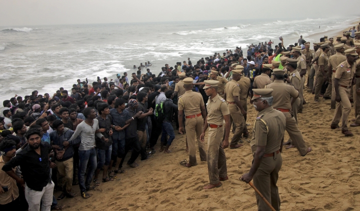Protestors supporting Jallikattu, a traditional bull-taming ritual try to form a human chain as police try to remove them from the Marina beach on the Bay of Bengal coast in Chennai, India, Monday, Jan.23, 2017. Protestors attacked a police station with stones and set some vehicles on fire Monday in anger at being forcibly evicted from the beach where they been protesting for the past week in support of the sport. Jallikattu involves releasing a bull into a crowd of people who attempt to grab it and ride it. It is popular in Tamil Nadu state, but India's top court banned it in 2014 on grounds of animal cruelty. (AP Photo)
