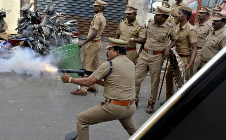 A police officer fires tear gas to disperse protestors in Chennai, India, Monday, Jan.23, 2017. Fans of Jallikattu, a traditional bull-taming ritual attacked a police station with stones and set some vehicles on fire Monday in anger at being forcibly evicted from the beach where they been protesting for the past week in support of the sport. Jallikattu involves releasing a bull into a crowd of people who attempt to grab it and ride it. It is popular in Tamil Nadu state, but India's top court banned it in 2014 on grounds of animal cruelty. (AP Photo)