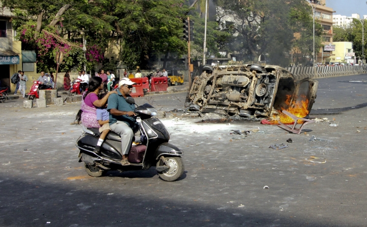A family on a scooter rides past as a vehicle suspected to be set on fire by protestors goes up in flames in Chennai, India, Monday, Jan.23, 2017. Fans of Jallikattu, a traditional bull-taming ritual attacked a police station with stones and set some vehicles on fire Monday in anger at being forcibly evicted from the beach where they been protesting for the past week in support of the sport. Jallikattu involves releasing a bull into a crowd of people who attempt to grab it and ride it. It is popular in Tamil Nadu state, but India's top court banned it in 2014 on grounds of animal cruelty. (AP Photo)