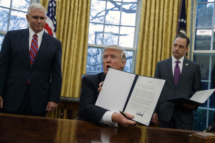 Vice President Mike Pence, left, and White House Chief of Staff Reince Priebus watch as President Donald Trump shows off an executive order to withdraw the U.S. from the 12-nation Trans-Pacific Partnership trade pact agreed to under the Obama administration, Monday, Jan. 23, 2017, in the Oval Office of the White House in Washington. (AP Photo/Evan Vucci)