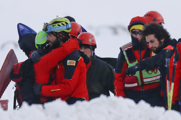 Rescuers hug each other on the site where an helicopter crashed, in the Campo Felice ski area, central Italy, Tuesday, Jan. 24, 2017. A helicopter ferrying an injured skier off the slopes crashed Tuesday in central Italy with at least six people aboard, another tragedy to hit a region slammed by recent earthquakes, heavy snowfall and an avalanche. (AP Photo/Gregorio Borgia)