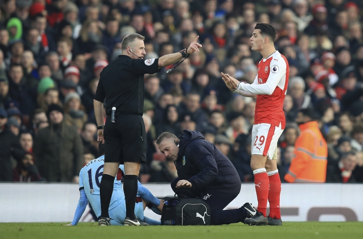 Burnley's Steven Defour, below, is left injured on the ground after a challenge from Arsenal's Granit Xhaka, right, for which he received a red card, during their English Premier League soccer match at The Emirates Stadium, London, Sunday, Jan. 22, 2017. (Mike Egerton/PA via AP)