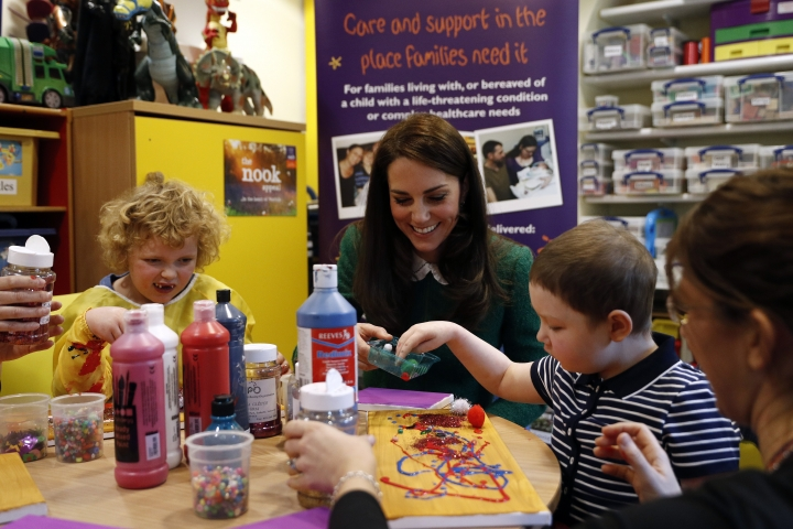 Britain's Kate, Duchess of Cambridge participates in a craft session with Isabella Benton, left, and Amy Hewett, second right, in the art therapy room during a visit to East Anglia's Children's Hospices (EACH) in Quidenham, near Norwich, eastern England, Tuesday Jan. 24, 2017. The Duchess toured the facilities of the hospice and met families who use the services at Quidenham. EACH offers support to families, and care for children and young people with life-threatening conditions in Norfolk. (Adrian Dennis/Pool via AP)