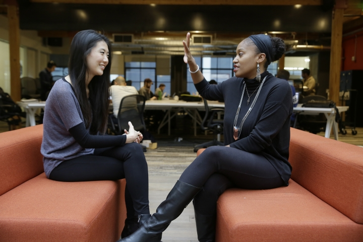 In this Tuesday, Jan. 3, 2017, photo, Aniyia Williams, founder and CEO of Tinsel, right, talks about program placement with Kara Lee, at the offices of Galvanize in San Francisco. Williams says she has made sure to hire women as well as underrepresented minorities. Tinsel makes tech jewelry targeted at women. (AP Photo/Eric Risberg)