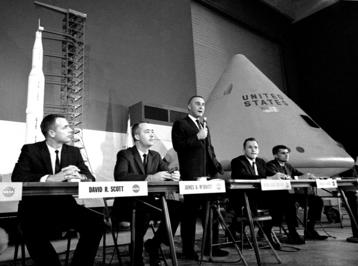In this Aug. 4, 1966 file photo, command pilot Virgil Grissom speaks during a news conference in Downey, Calif., with a mockup of the Apollo spacecraft at right. Grissom's crewmen are Roger B. Chaffee, right, and Edward H. White, second from right. Two of the three back-up crew members are, from left, David R. Scott and James A. McDivitt. (AP Photo/George Brich)