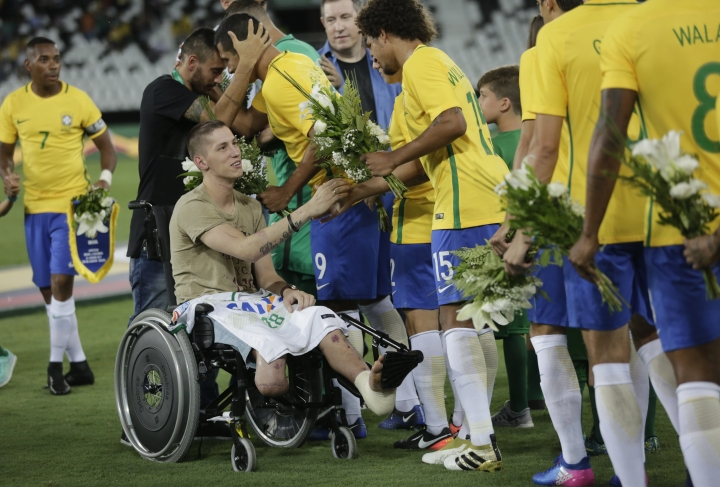 Former Chapecoense goalkeeper Follmann, in wheelchair, and Alan Ruschel, behind him, greet Brazils' soccer players prior to a friendly match with Colombia at the Nilton Santos stadium, in Rio de Janeiro, Brazil, Wednesday, Jan 25, 2017. The match is a tribute to Chapecoense soccer players who died in a plane crash in Colombia last November. Follmann and Ruschel survived the crash. (AP Photo/Silvia Izquierdo)