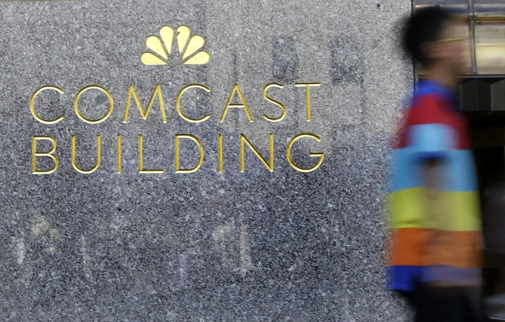 FILE - In this July 23, 2015, file photo, a man walks past the Comcast Building in New York. In the next few months, cable giant Comcast will start selling wireless service, just as AT&T and Verizon already do. (AP Photo/Mary Altaffer, File)