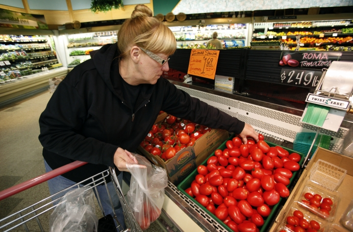 FILE - In this March 23, 2011 file photo, a woman shops for tomatoes at a grocery store in Des Moines, Iowa. Scientists have cooked up a way to reintroduce a key ingredient into mass-produced tomatoes: taste. Researchers have figured out just the right spots on the genetic blueprint of tomatoes where flavor has been bred out of supermarket tomatoes for the past 40 or 50 years, according to a study in the journal Science. And using natural breeding methods, a little modernized with hand pollination by electric toothbrushes _ they are reinstalling five factors to add aroma and taste into the staple of salads. (AP Photo/Charlie Neibergall, File)