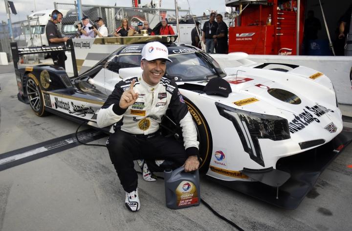 Joao Barbosa, of Portugal, poses next to his Cadillac DPi after he won the pole position for the IMSA 24-hour auto race at Daytona International Speedway, Thursday, Jan. 26, 2017, in Daytona Beach, Fla. (AP Photo/John Raoux)