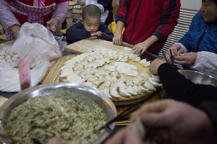 A child watches as adults make dumplings ahead of the Chinese lunar new year at a village on the outskirts of Beijing, China, Thursday, Jan. 26, 2017. Chinese in mainland China hand make and eat dumplings to mark the start of the Year of the Rooster on Jan 28, 2017. (AP Photo/Ng Han Guan)