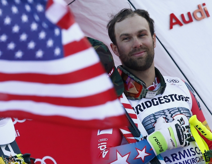The winner Travis Ganong, of the United States, celebrates on podium after an alpine ski, men's World Cup downhill race, in Garmisch Partenkirchen, Germany, Friday, Jan. 27, 2017. (AP Photo/Giovanni Auletta)