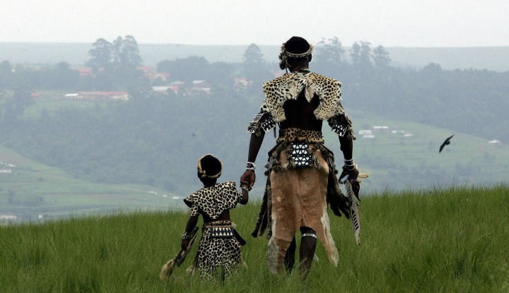 FILE - In this Jan. 15, 2016 file photo a man and his son, members of the Shembe Church, dressed in tribal leopard skins at the end of a pilgrimage on the holy Nlangakazi Mountain north of Durban, South Africa. In a gathering this weekend many worshippers will wear leopard skins, seen as symbols of status and power. Some of the pelts to be displayed, however, are fake, reflecting an effort by an international conservation group to reduce poaching of Africa's threatened leopards. (AP Photo/Themba Hadebe, File)