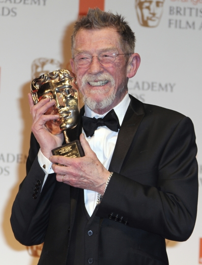 """File - This Feb. 12, 2012, file photo shows actor Sir John Hurt posing with his award for """"Outstanding Contribution to Cinema"""" backstage at the BAFTA Film Awards 2012, at The Royal Opera House in London. The great and versatile actor Hurt, who could move audiences to tears in """"The Elephant Man,"""" terrify them in """"Alien,"""" and spoof that very same scene in """"Spaceballs,"""" has died at age 77. Hurt, who battled pancreatic cancer, passed away Friday, Jan. 27, 2017, in London according to his agent Charles McDonald. (AP Photo/Joel Ryan, File)"""