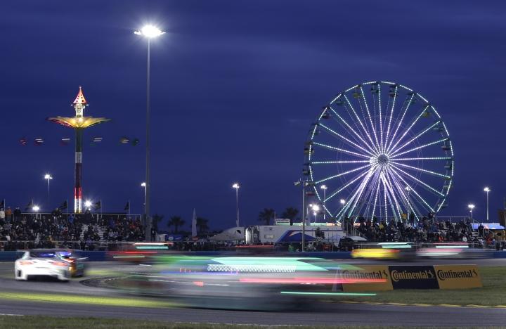 Cars races around the east horseshoe turn as darkness sets in at the IMSA 24-hour auto race at Daytona International Speedway, Saturday, Jan. 28, 2017, in Daytona Beach, Fla. (AP Photo/John Raoux)