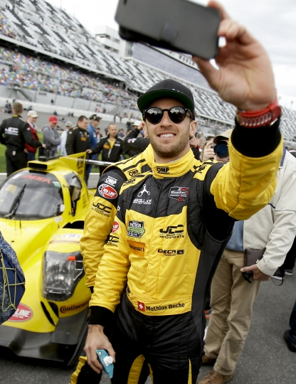 Mathais Beche, of Switzerland, takes a selfie photo in front of his car before the start of the IMSA 24-hour auto race at Daytona International Speedway, Saturday, Jan. 28, 2017, in Daytona Beach, Fla. (AP Photo/John Raoux)