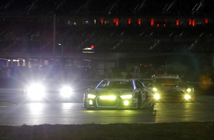 Cars race to the east horseshoe turn during the evening hours of the IMSA 24-hour auto race at Daytona International Speedway, Saturday, Jan. 28, 2017, in Daytona Beach, Fla. (AP Photo/John Raoux)