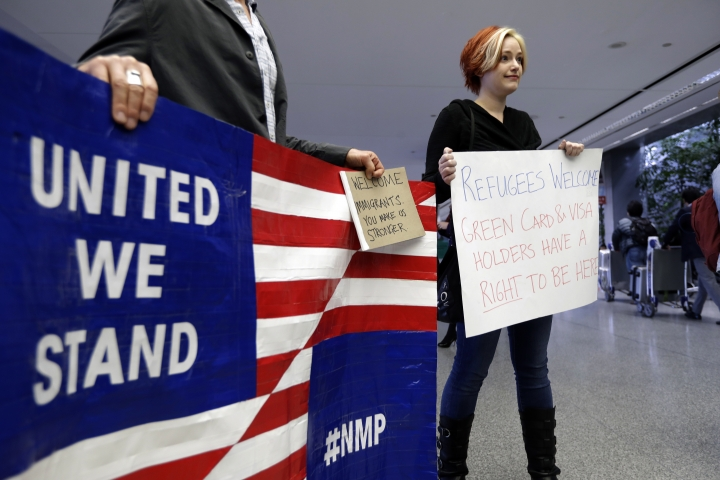Robert May, left, and Sarah Dizio hold signs in the arrivals terminal at San Francisco International Airport to protest President Donald Trump's executive order that bars citizens of seven predominantly Muslim-majority countries from entering the U.S. Monday, Jan. 30, 2017, in San Francisco. (AP Photo/Marcio Jose Sanchez)