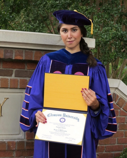 CORRECTS SOURCE OF PHOTO TO NAZANIN ZINOURI - In this undated photo provided by Nazanin Zinouri, she poses for a photo with her PhD degree from Clemson University in Clemson, S.C. Zinouri, who has a visa and has lived in the U.S. since August 2010, flew to Iran on Jan. 20, 2017, expecting to have three weeks of family time with her mother, brother and sister. Instead, she was barely in Tehran before she began trying to get home to South Carolina following President Donald Trump's order barring entry to people from Iran and six other Muslim countries. (Courtesy of Nazanin Zinouri via AP)