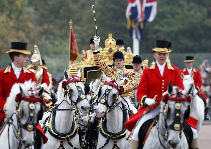 FILE - In this file photo dated Tuesday, Nov. 1, 2016, the leading groom gestures as the procession with Britain's Queen Elizabeth II and the President of Colombia Juan Manuel Santos arrive by carriage at Buckingham Palace in London. The invitation to U.S. President Donald Trump for a state visit, one of the highest honors it can bestow on a visiting statesman where the queen acts as personal hostess with the traditional pomp and ceremony involved, has provoked a passionate debate, Tuesday Jan. 31, 2017. (AP Photo/Alastair Grant, FILE)