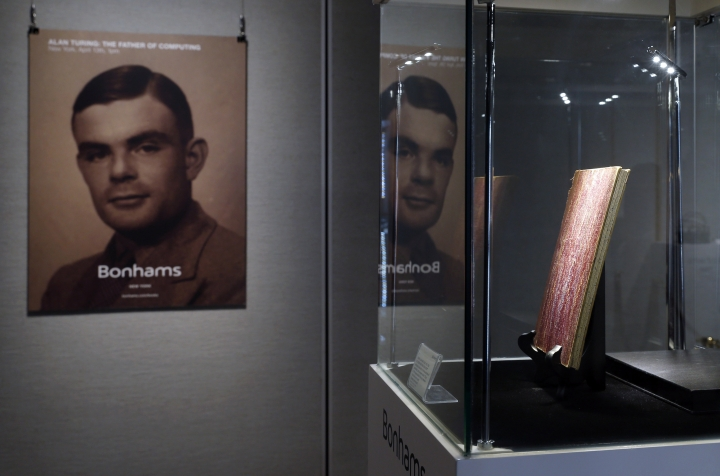 "FILE - In this Thursday, March 19, 2015 file photo, a notebook of British mathematician Alan Turing is displayed in front of his portrait during an auction preview in Hong Kong. Thousands of men convicted under now-abolished anti-homosexuality laws in Britain have been pardoned posthumously under a law passed on Tuesday, Jan. 31, 2017 and many more still alive can now apply to have their criminal convictions wiped out. Calls for a general pardon have noted the 1954 suicide of World War II codebreaking hero Alan Turing after his conviction for ""gross indecency."" After he received a posthumous royal pardon in 2013, pressure for pardons intensified. (AP Photo/Kin Cheung, file)"