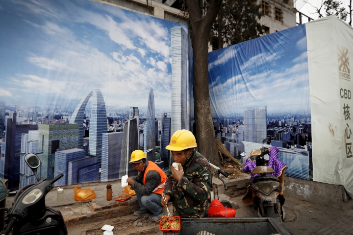 In this Dec. 13, 2016 photo, workers eat their lunch outside a construction site wall depicting the skyline of the Chinese capital at the Central Business District in Beijing. Chinese manufacturing expanded in January at close to its fastest pace in two years as heavy government spending and a bank lending boom helped to keep economic activity steady headed into 2017, a survey showed Wednesday, Feb. 1, 2017. (AP Photo/Andy Wong)