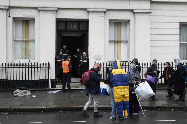 Court appointed bailiffs control access to a building as people are evicted from a large mansion in Eaton Square, a fashionable part of London near Buckingham Palace, on Wednesday, Feb. 1, 2017. British authorities have evicted a group of squatters who moved into a vacant mansion in one of London's priciest neighborhoods to draw attention to the problem of homelessness. (AP Photo/Alastair Grant)