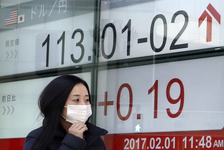 A woman walks past an electronic stock indicator of a securities firm showing the currency rate of the U.S. dollar that is traded at 113.01-02 yen in Tokyo, Wednesday, Feb. 1, 2017. Shares were mostly higher in Asia on Wednesday, lifted by upbeat manufacturing data from China and Japan. (AP Photo/Shizuo Kambayashi)