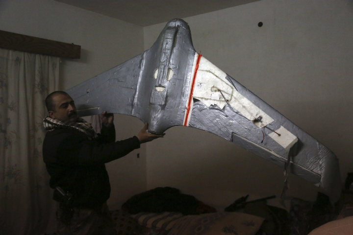 In this Friday, Jan. 27, 2017 photo, an Iraqi officer holds a drone belonging to Islamic State militants in Mosul, Iraq. Islamic State is hacking store-bought drone technology, using rigorous testing and tactics that mimic those used by U.S. unmanned aircraft to adapt to diminishing numbers of fighters and a battlefield that is increasingly difficult to navigate on the ground. (AP Photo/Khalid Mohammed)
