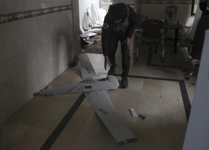 In this Saturday, Jan. 28, 2017 photo, an Iraqi officer inspects a drone belonging to Islamic State militants in Mosul, Iraq. Islamic State is hacking store-bought drone technology, using rigorous testing and tactics that mimic those used by U.S. unmanned aircraft to adapt to diminishing numbers of fighters and a battlefield that is increasingly difficult to navigate on the ground. (AP Photo/ Khalid Mohammed)