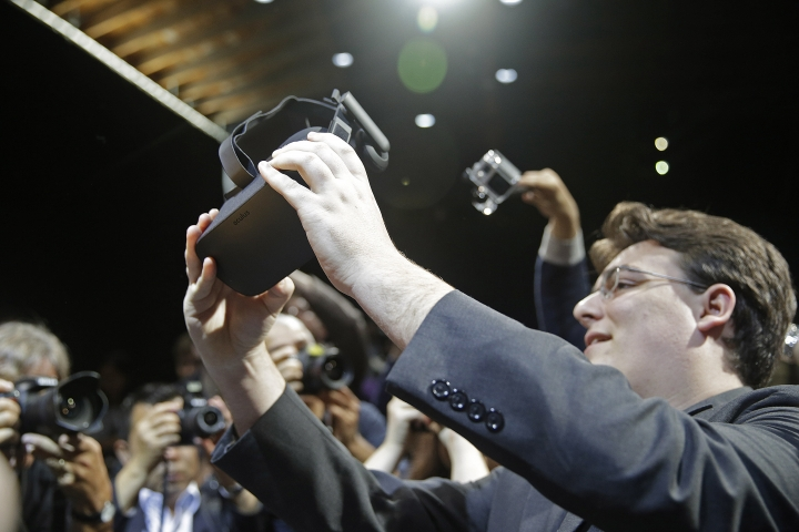FILE - In this June 11, 2015, file photo, Oculus founder Palmer Luckey holds up the new Oculus Rift virtual reality headset for photographers following a news conference, in San Francisco. In a verdict reached Wednesday, Feb. 1, 2017, Facebook's virtual-reality subsidiary and two of its founders, Luckey and Brendan Iribe, are facing a sobering reality after a jury hit them with a $500 million bill for infringing on the rights of a video-game maker. (AP Photo/Eric Risberg, File)