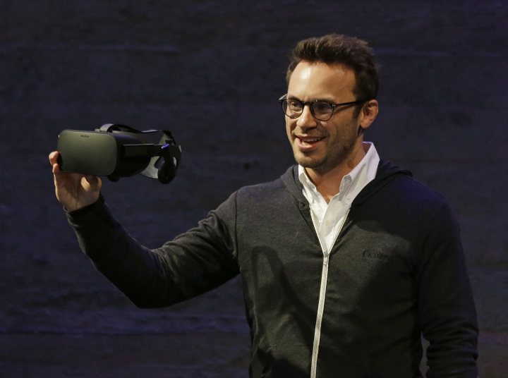 FILE - In this Thursday, June 11, 2015, file photo, Oculus CEO Brendan Iribe holds up the Rift virtual reality headset during a news conference in San Francisco. In a verdict reached Wednesday, Feb. 1, 2017, Facebook's virtual-reality subsidiary and two of its founders, Iribe and Palmer Luckey, are facing a sobering reality after a jury hit them with a $500 million bill for infringing on the rights of a video-game maker. (AP Photo/Eric Risberg, File)
