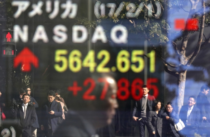 People are reflected on an electronic stock indicator of a securities firm in Tokyo, Thursday, Feb. 2, 2017. Asian markets wavered and the dollar lost some steam Thursday after the Fed kept its key lending rate on hold as expected at its latest policy meeting. (AP Photo/Shizuo Kambayashi)