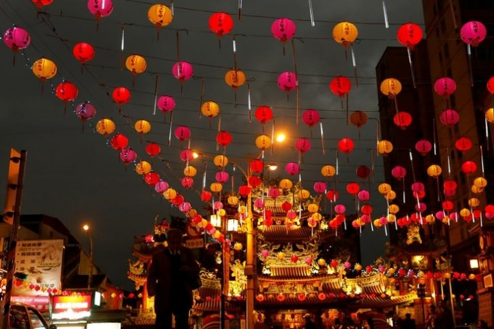 A tourist walks under the lanterns along a street ahead of the Chinese Lunar New Year outside Raohe street Night Market in Taipei, Taiwan January 18, 2017. REUTERS/Tyrone Siu