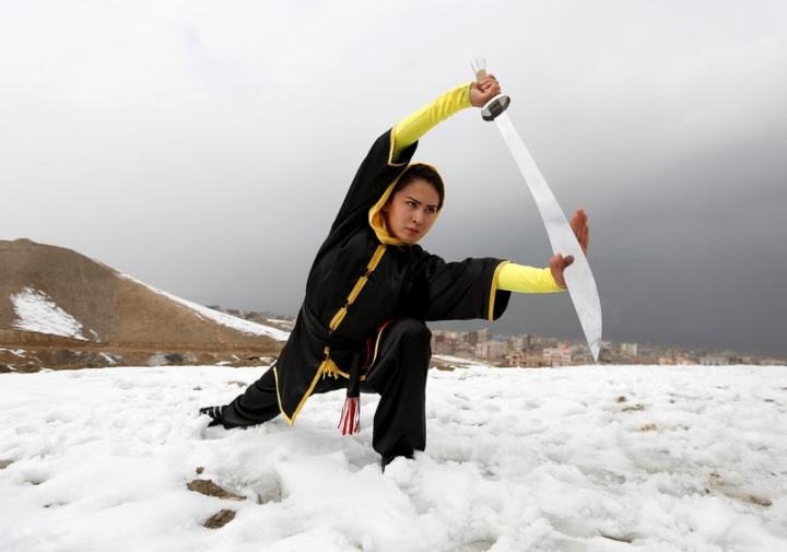 Sima Azimi, 20, a trainer at the Shaolin Wushu club, shows her Wushu skills to other students on a hilltop in Kabul, Afghanistan January 29, 2017. REUTERS/Mohammad Ismail