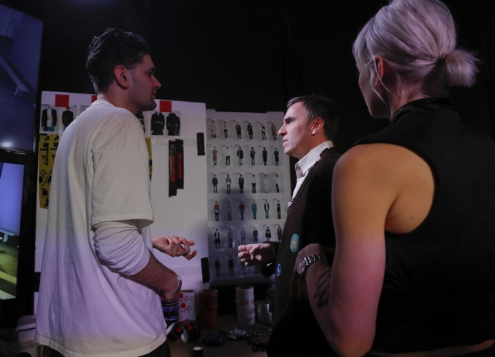Designer Raf Simons, center, talks with assistants before the start of the Raf Simons men's collection runway show during Men's Fashion Week, Wednesday, Feb. 1, 2017, in New York. (AP Photo/Julie Jacobson)