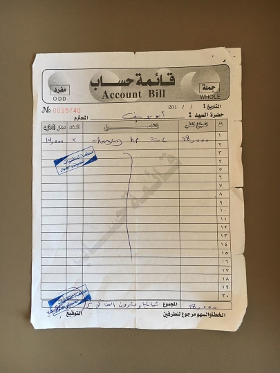 "This Thursday, Feb. 2, 2017 photo shows a receipt for two chargers for Hewlett Packard computers. The paper is stamped from the ""Mecca shop for computers, technology and mobile phones,"" and the total amount is 28,000 Iraqi dinars or about 20 dollars. (AP Photo)"