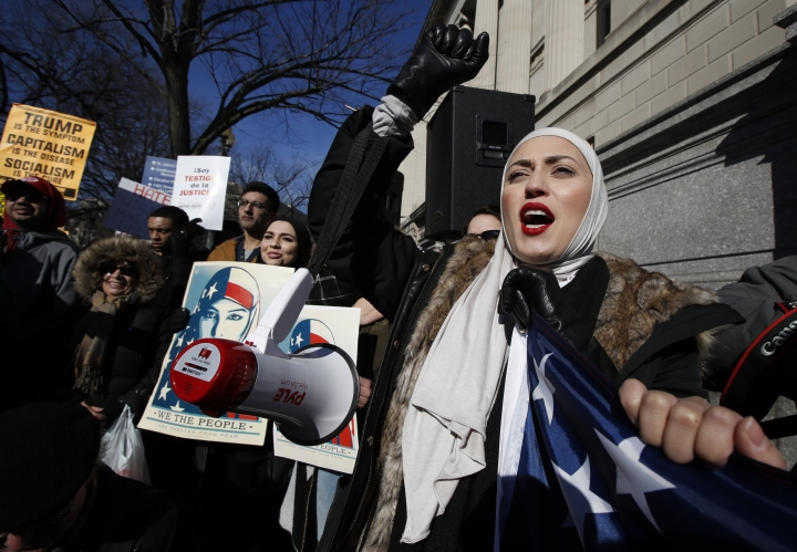 A demonstrator chants during a rally protesting the immigration policies of President Donald Trump, near the White House in Washington, Saturday, Feb. 4, 2017. (AP Photo/Manuel Balce Ceneta)