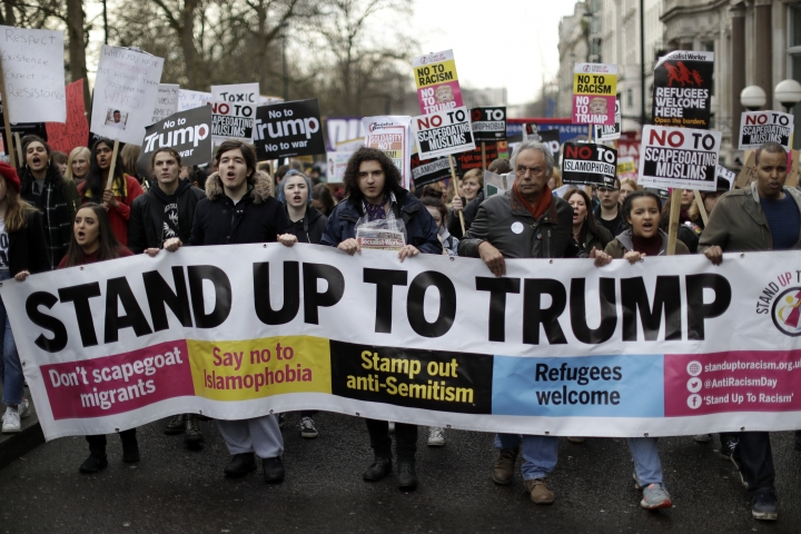 People hold a banner as they take part in a protest march in London, against U.S. President Donald Trump's ban on travellers and immigrants from seven predominantly Muslim countries entering the U.S., Saturday, Feb. 4, 2017. Thousands of protesters have marched on Parliament in London to demand that the British government withdraw its invitation to U.S. President Donald Trump. (AP Photo/Matt Dunham)