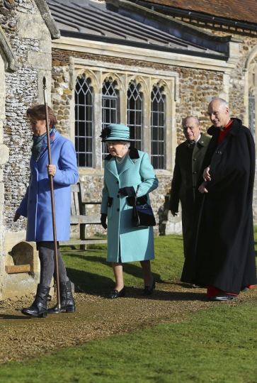 Britain's Queen Elizabeth II and her husband Duke of Edinburgh, centre, are escorted as they arrive at St Peter and St Paul church in West Newton, England, Sunday Feb. 5, 2017. The Queen is to make history on Monday Feb. 6, when she becomes the first British monarch to reach the Sapphire Jubilee, marking the 65th. anniversary of her accession to the throne. (Gareth Fuller/PA via AP)
