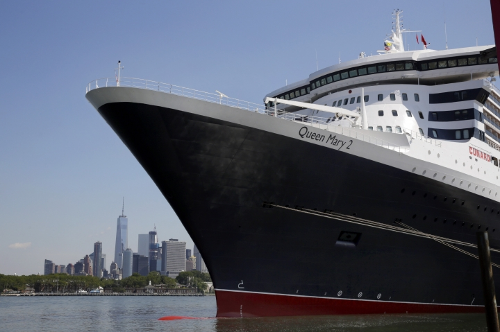 FILE - In this July 6, 2016, file photo, the New York City skyline appears behind the ocean liner Queen Mary 2 as she sits docked at her homeport at the Brooklyn Cruise Terminal in New York. The ship will offer a trans-Atlantic fashion-themed crossing from England to New York Aug. 31-Sept. 7 with celebrity guests including the 95-year-old style icon Iris Apfel. (AP Photo/Richard Drew, File)