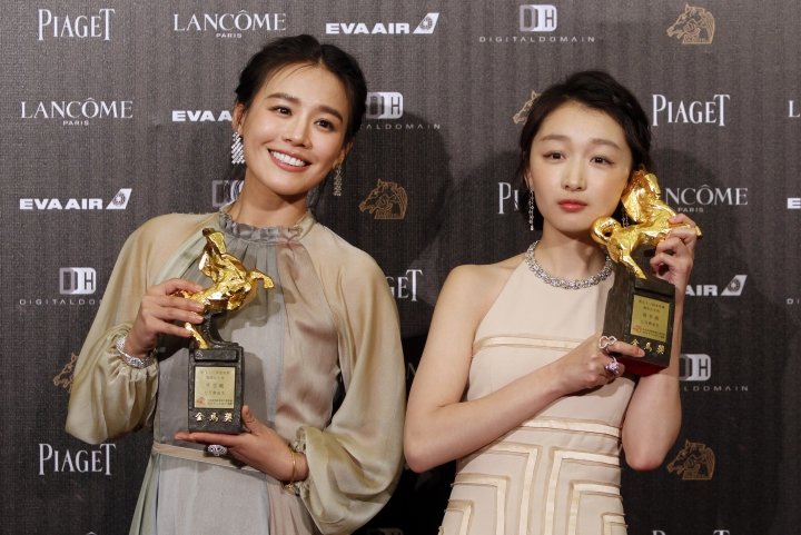 """FILE - In this Saturday, Nov. 26, 2016, file photo, Chinese actress Zhou Dongyu, right, and Ma Sichun hold their award for Best Leading Actress at the 53rd Golden Horse Awards in Taipei, Taiwan. Romance drama """"Soul Mate"""" has charmed the Hong Kong Film Awards. The coming-of-age tale of two girls falling for the same boy received 12 nominations, with Zhou and Ma both getting nods in the best actress category. The awards ceremony is on April 9. (AP Photo/Billy Dai)"""