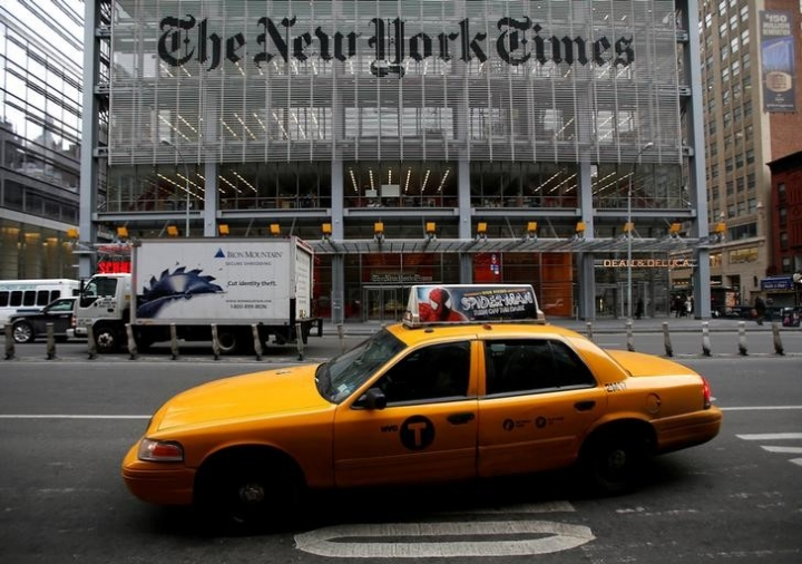 FILE PHOTO -  A taxi passes by in front of The New York Times head office in New York, February 7, 2013.  REUTERS/Carlo Allegri/File Photo