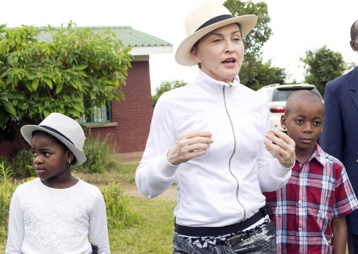 """FILE -- In this Friday, April 5, 2013 file photo Madonna, center, tours the Mphandura orpahange near Lilongwe, Malawi with her two adopted children David Banda, right and Mercy James, left. Court documents in Malawi say Madonna was asked """"uncomfortable questions"""" by a judge during the pop star's successful application to adopt twins from the country in southern Africa Tuesday, Feb. 7 2017. (AP Photo/Thoko Chikondi, File)"""