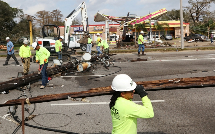 Cleanup crews remove power poles from Chef Menteur highway in New Orleans East after a series of tornados tore through the city and other parts of Louisiana, leaving trees, power lines, homes and businesses leveled, in New Orleans, Louisiana, U.S., February 8, 2017.  REUTERS/Ben Depp